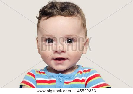 Portrait of a cute baby boy sitting and smiling. Adorable six month old child happy laughing.