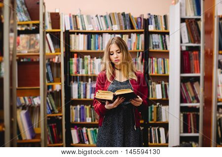 Female student reading book between bookshelves in university library