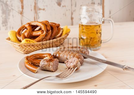 Bavarian cooked sausage and pretzel on a breadbasket and beer on background