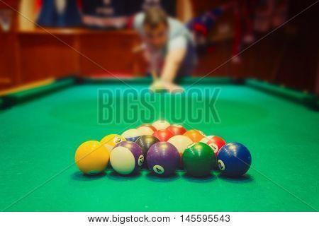 Colorful billiard balls on green pool table