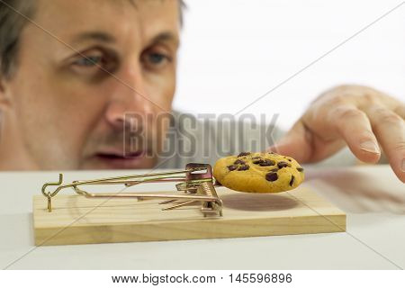 Close up shot of a man looking eagerly at eating a sweet cookie that is in a mouse trap which indicates that he should not eat it or is on a diet.