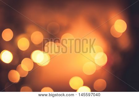 Festive warm bokeh with sparkling Christmas lights in orange colors as Christmas background
