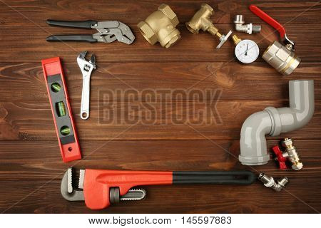 Plumber tools frame on wooden background