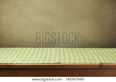 Wooden table with checked green tablecloth background