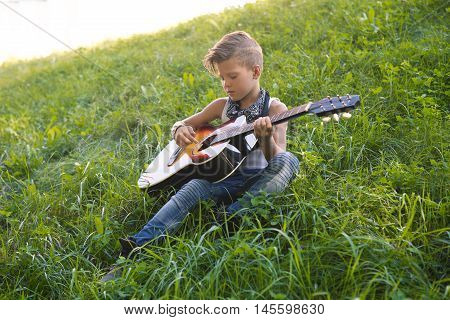 Little boy sitting on the grass and plays the guitar . A boy learns to play the guitar . It is stylish. Learning music and guitar