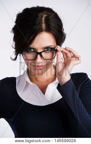Young business woman looking skeptically over her spectacles, over white background.