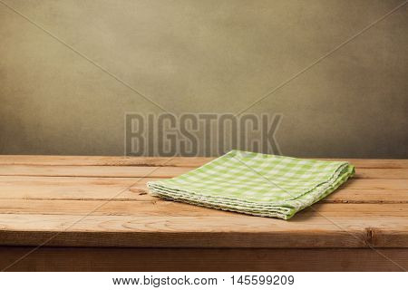 Empty wooden table with checked green tablecloth