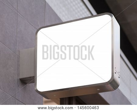 Blank metal shop sign board on building wall