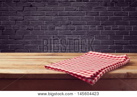Wooden counter background with red checked tablecloth over black brick wall