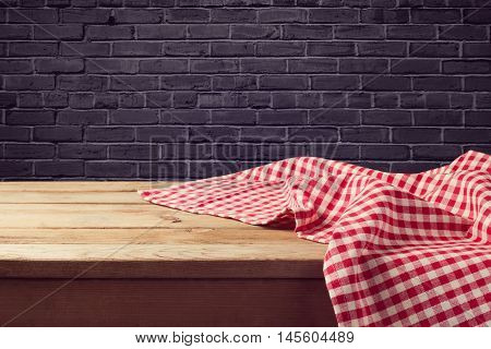 Wooden table background with red checked tablecloth over black brick wall