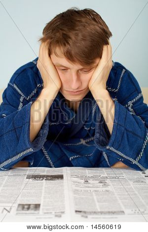 Sad man reading a newspaper at home in his dressing gown poster