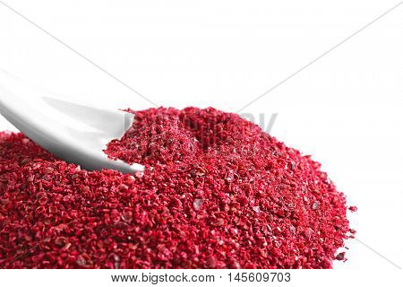 Heap of sumac with spoon on white background