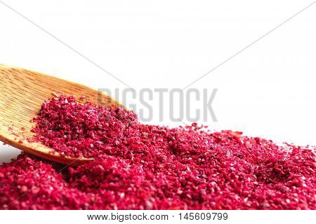 Sumac and wooden spoon on white background