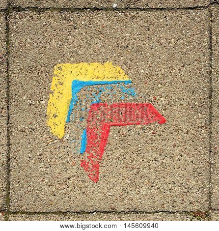 Paving stone with three painted arrow heads yellow blue and red symbolising bauhaus.