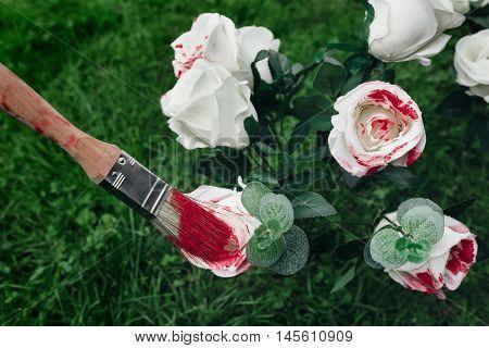 White roses and paintbrush. Based on Alice in Wonderland