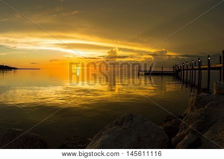 Sunset bayside over the Florida Keys. Boat dock with a reflection
