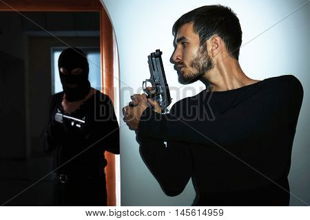 Armed thieves entering a house and man defending his property