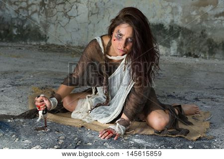 Dangerous woman in rags sitting in a derelict building with a bloody knife