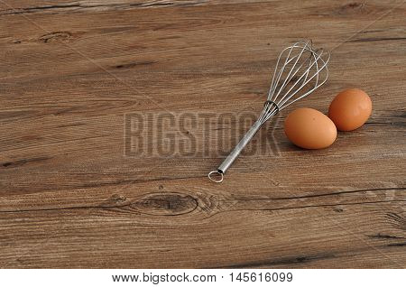An egg beater whisk with two eggs isolated on a wooden background