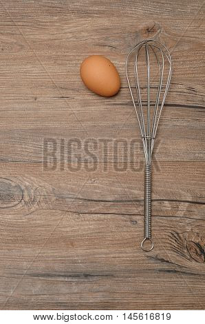 An egg beater whisk with one egg isolated on a wooden background