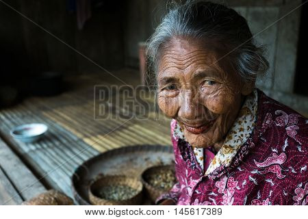 FLORES, INDONESIA - AUGUST 22, 2016: A woman takes a short break from cleaning coffee beans in Bena traditional village in Bajawa, Flores, Indonesia.