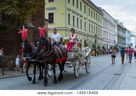 KRAKOW, POLAND - SEP 4, 2016: Old-styled carriage for tourists in the streets of Old Krakow. Krakow is visited by over 8 million tourists a year, number of foreign tourists up to 2 million people.
