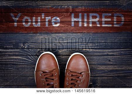 You're Hired message and sport shoes on wooden floor