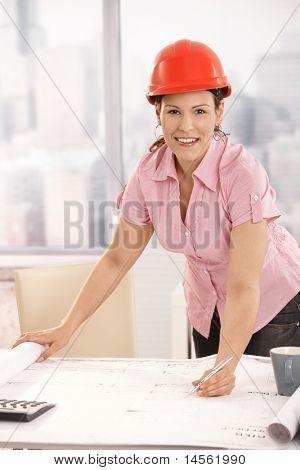 Junge Architekt arbeiten am Schreibtisch, Schreiben von Notizen auf Grundriss. Blick in die Kamera Lächeln.?