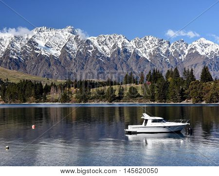 Queenstown New Zealand - Aug 27 2016. Small yacht on the Lake Wakatipu. The Remarkables mountains in the background.