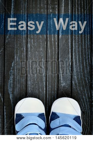 Easy Way message and kid shoes on wooden floor
