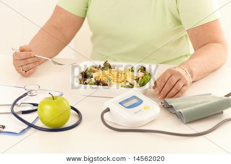 Elderly woman eating healthy diet, salad and apple.?