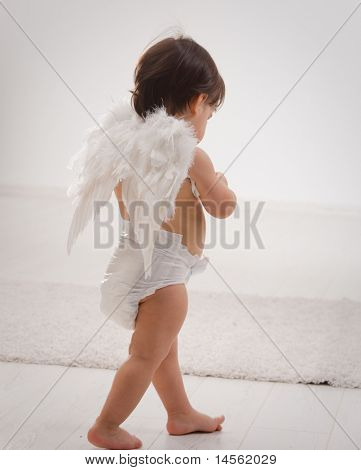 One year old baby girl wearing white angel wings. Back view. Isolated on white background.?