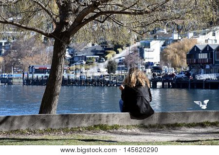 Queenstown, New Zealand - Aug 27, 2016. Girl sitting at Lake Wakatipu Saturday afternoon in winter.