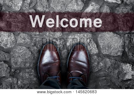 Welcome message on asphalt and business shoes