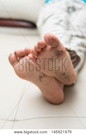 boy lying on sofa with dirty feet