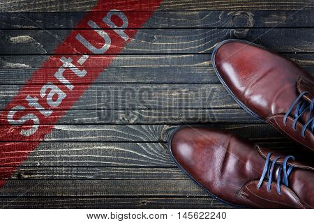Start-up message and business shoes on wooden floor