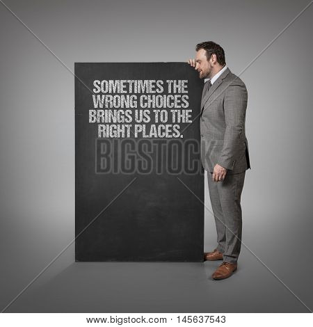 Sometimes the wrong choices brings us to the right places. text on blackboard with businessman standing side