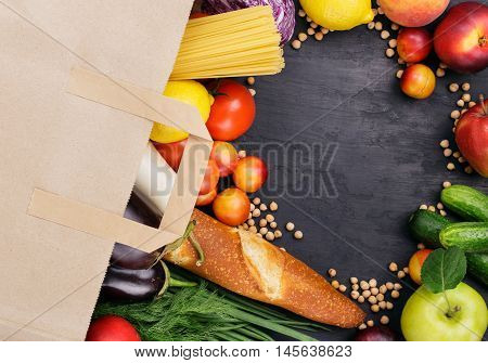 Full paper bag with different helpful food on dark surface with copy space top view