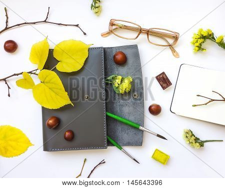 Closeup of leather pen case and art accessories and glasses on white background. Decorated with autumn yellow leaves flowers and branches. Top view flat lay