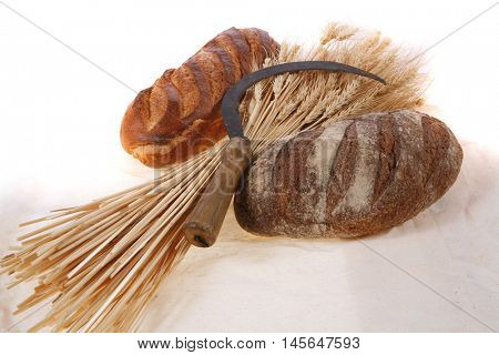 bunch of mown wheat ears with vintage handmade reaper hook sickle and rye and white dark french fresh bread loaf on light linen tablecloth