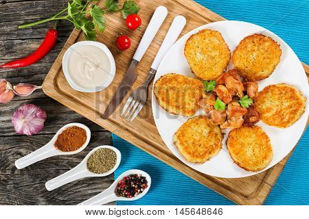 Crispiest Shredded Potatoes Hash Browns with fried meat and onion on white plate on cutting board on table mat spices in porcelian spoons on wooden table view from above
