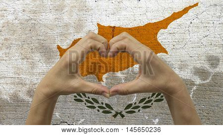 With a stylized Cypriot flag background an anonymous person's hands being held in the form of a heart symbolizing love and patriotism for Cyprus.