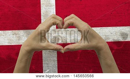 With a stylized Danish flag background an anonymous person's hands being held in the form of a heart symbolizing love and patriotism for Denmark.