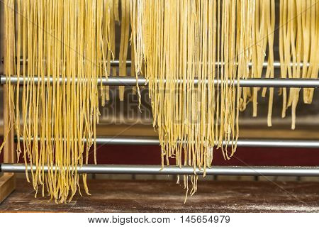 Closeup homemade noodles drying on aluminum support