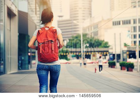 young asian woman walking on city street