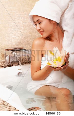 Beautiful asian woman holding lotus at the spa