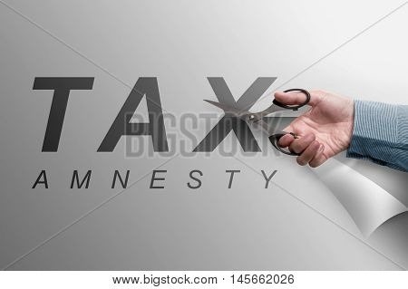 The Hand Cutting The Paper That Reads Tax Amnesty