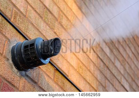 Steam coming out of a central heating flue on a house wall England UK Western Europe.