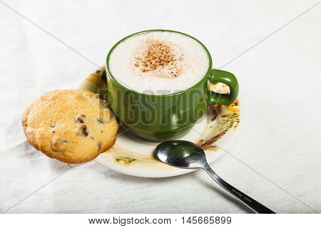 Green cup with chocolate spoon and cookies
