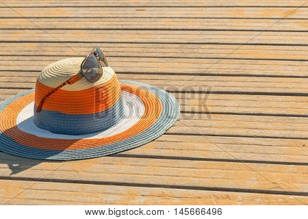 Colored straw hat set on a wooden floor at the beach